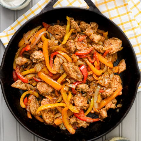 A cast iron skillet, filled with chicken fajita ingredients: chicken breast, sliced peppers, and onions. The skillet rests on a tea towel, and adjacent to a bowl of sour cream, as well as a bowl of shredded cheese.