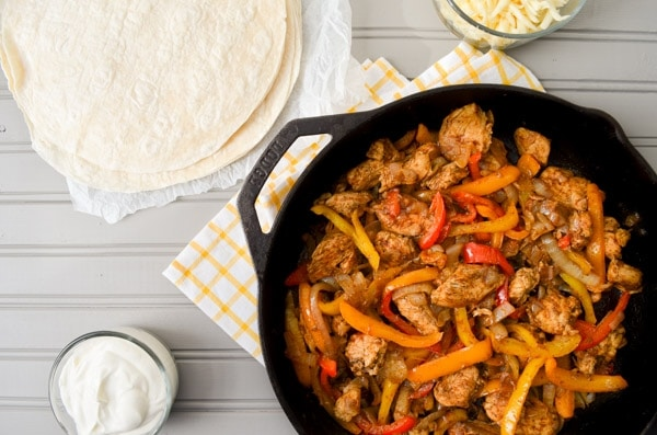 A cast iron skillet is filled with chicken breasts, sliced peppers, and onions. On the table next to it rests a bowl of sour cream, shredded cheese, and flour tortillas.