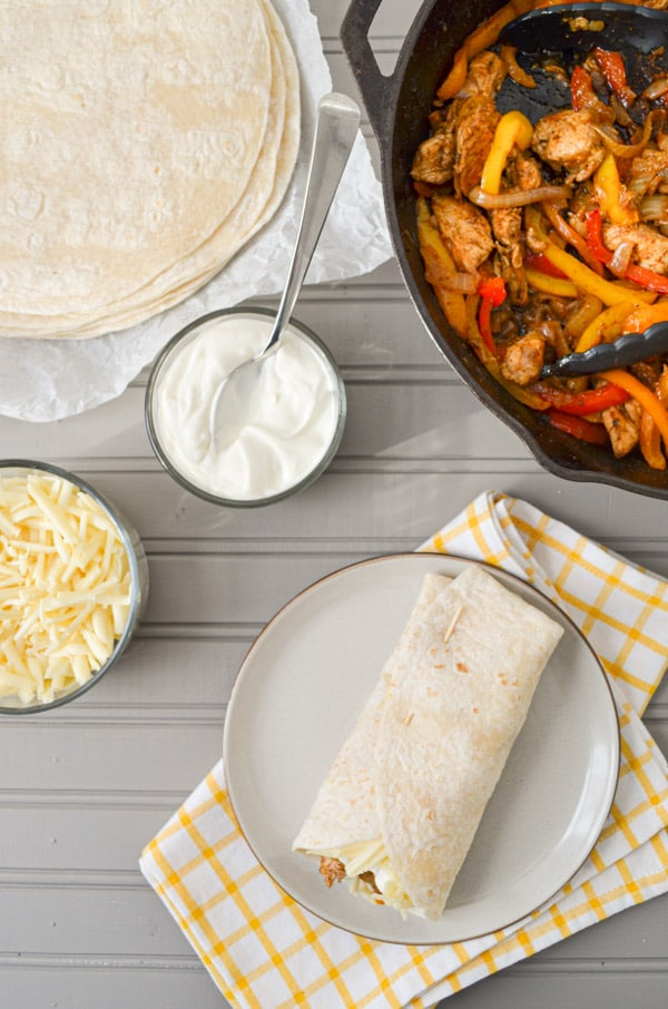 A grey wood table with all of the fixings for chicken fajitas, including shredded cheese, sour cream, and tortillas. A cast iron skillet is in the top right corner, containing chicken fajitas.