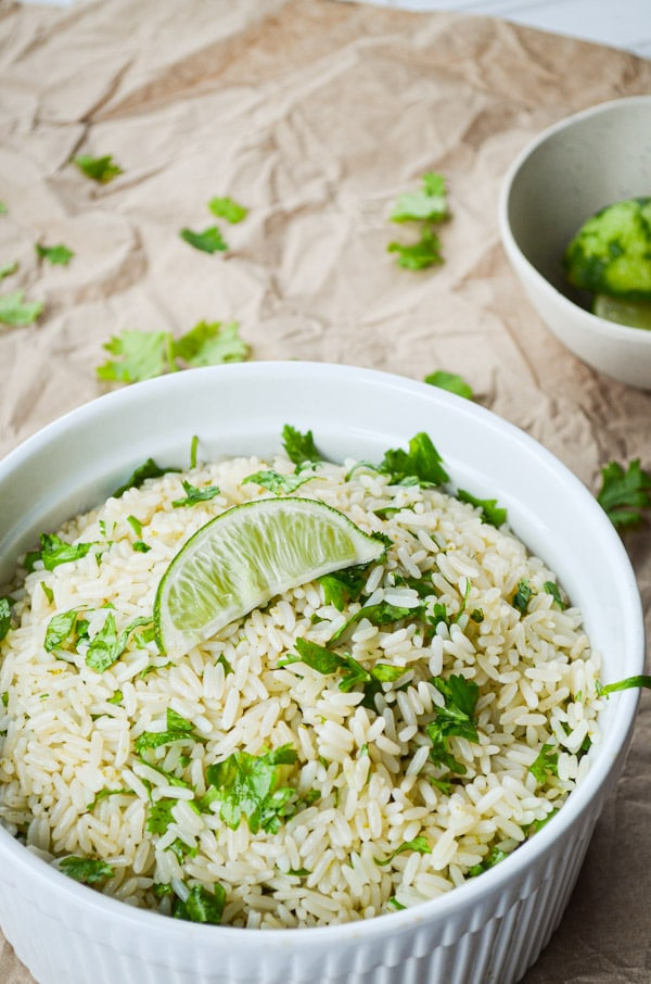 A dish full of cilantro lime rice on a brown paper covered table. Garnished with a lime wedge.