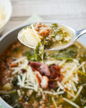 A bowl of zuppa toscana, with a spoonful of soup.