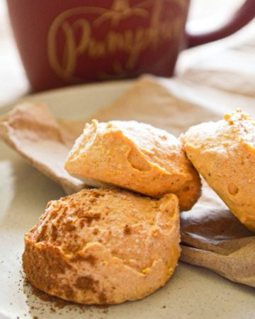 Pumpkin cheesecake bites, with a mug in the background.