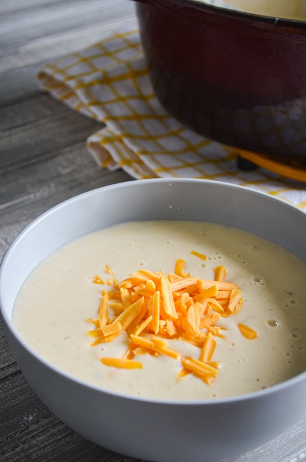 A bowl of leftover mashed potato soup, sprinkled with shredded cheddar cheese.