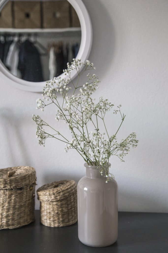 A vase of flowers on a dresser, with two small baskets.