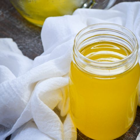 A jar of homemade instant pot ghee, surrounded by a white cloth towel.