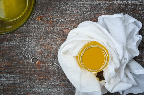 A jar of golden ghee in flatlay, surrounded by a white kitchen towel, and a bowl of freshly made Instant Pot Ghee.