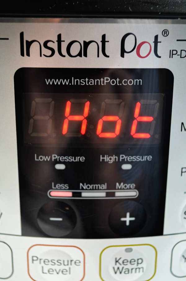 """An Instant Pot with the digital screen reading """"hot"""""""