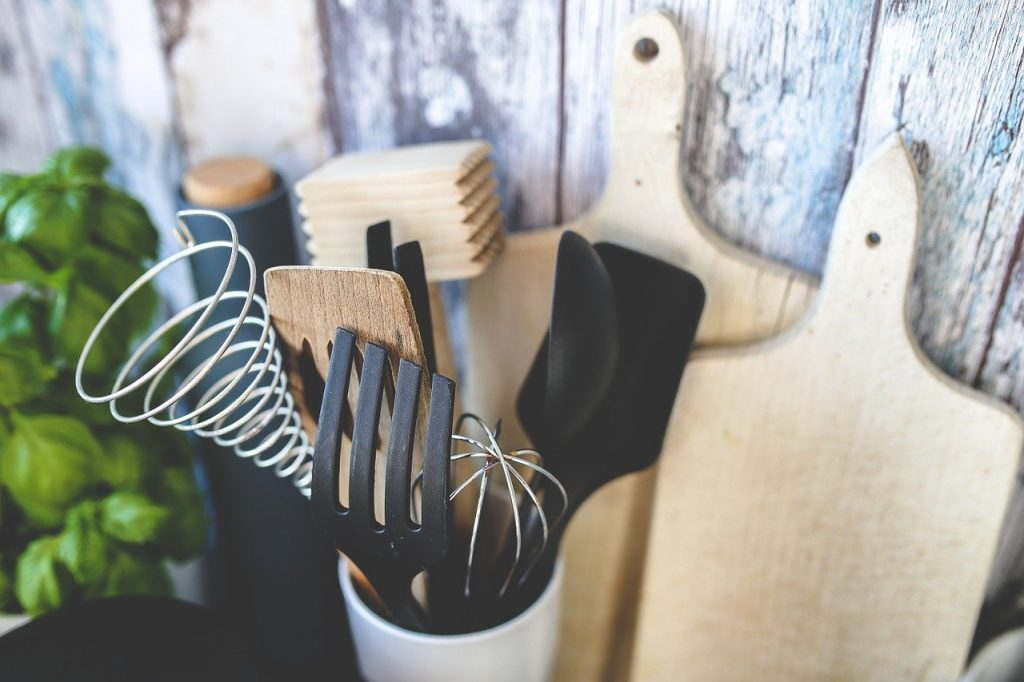 Wooden cutting boards and utensils, against a backdrop of wood.