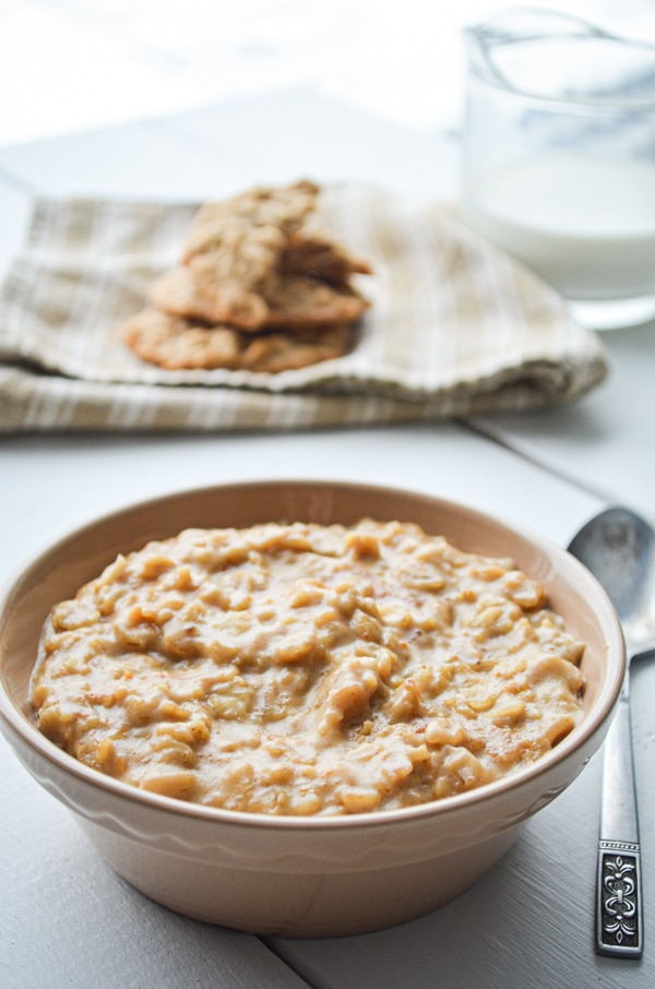 A bowl of peanut butter cookie oatmeal, with peanut butter cookies and a cruet of milk in the background.