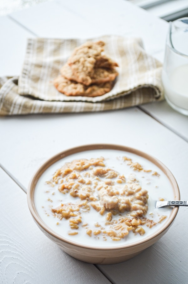A bowl of peanut butter cookie oatmeal, served with plenty of milk.