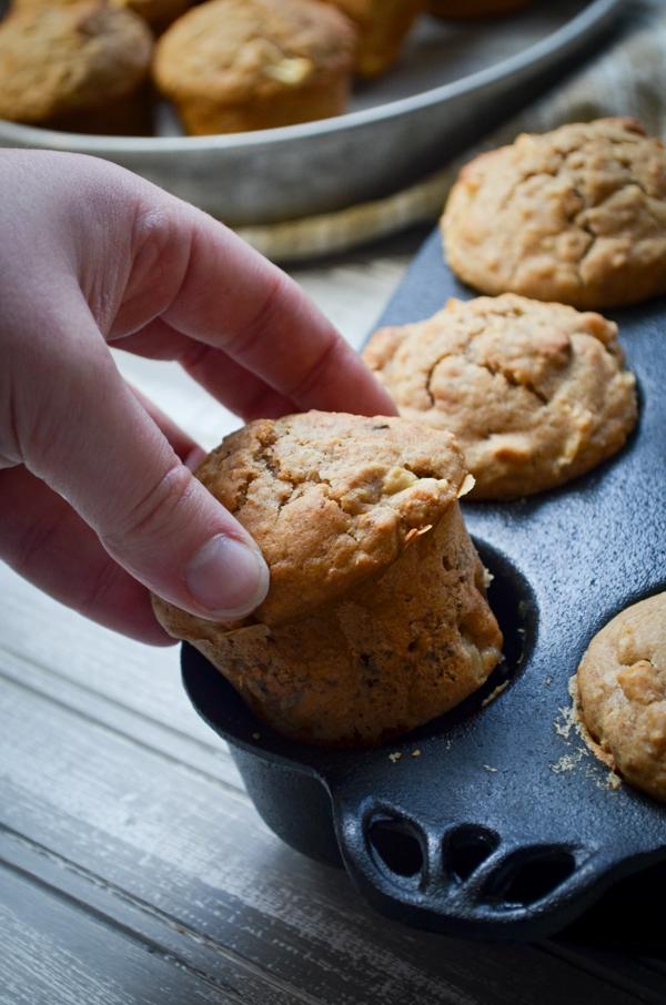 A hand pulls a sourdough muffin from a cast iron muffin pan.