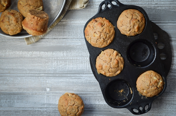 A cast iron muffin pan, holding 4 sourdough muffins.