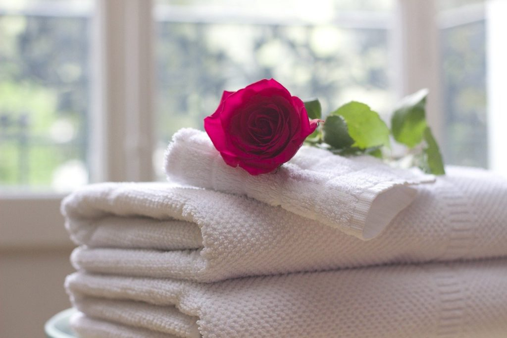 Towels folded with a rose on top.