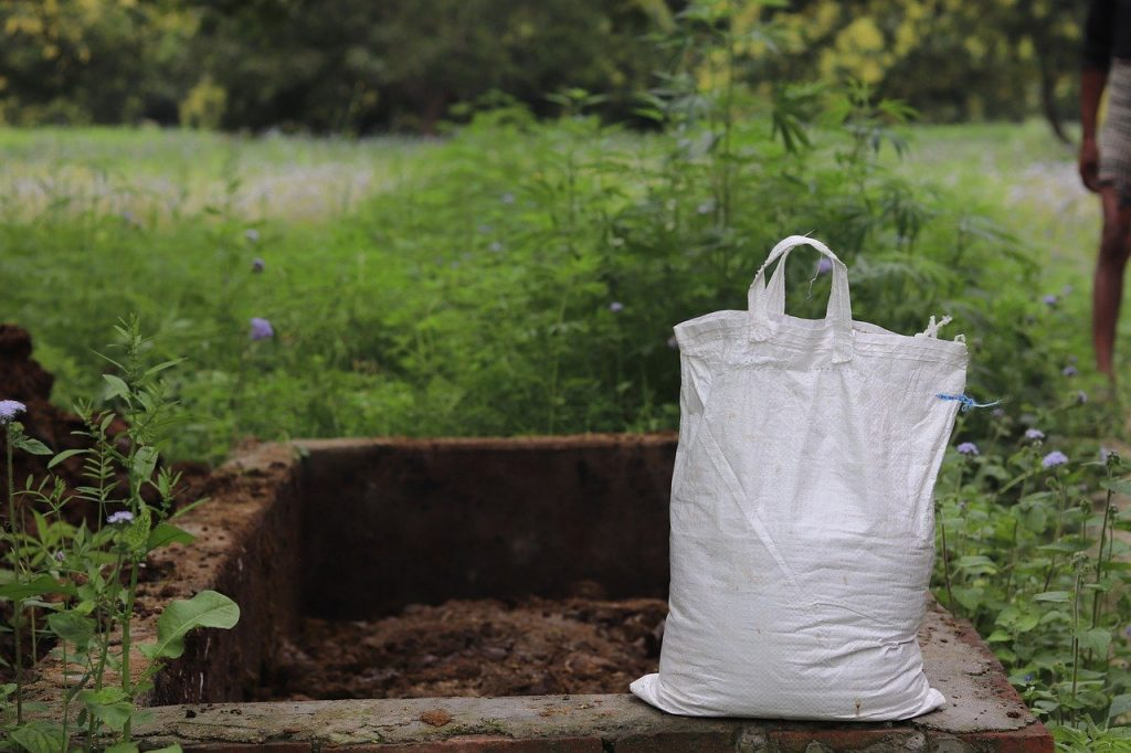 A large feed bag, filled with compost, sits on the ledge of a stone-edged compost pile. Purchasing and ordering compost is a great way to prepare for gardening season.