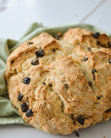 A loaf of Irish Soda bread lays on top of a green cloth napkin. A large cross is cut in the center and it is dotted with raisins.