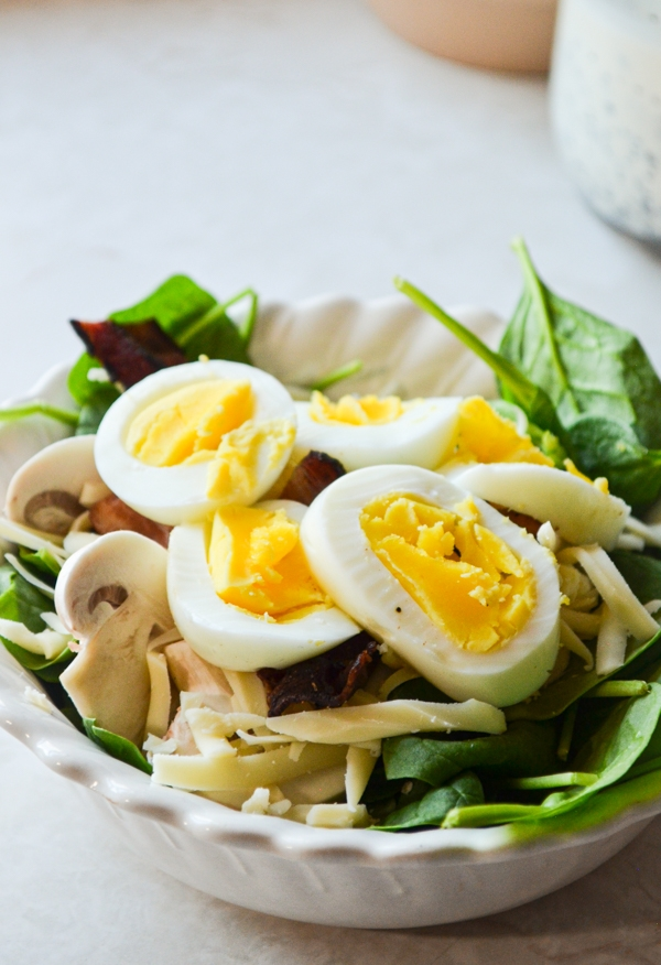 A small bowl of baby spinach salad, topped with hard-boiled eggs.