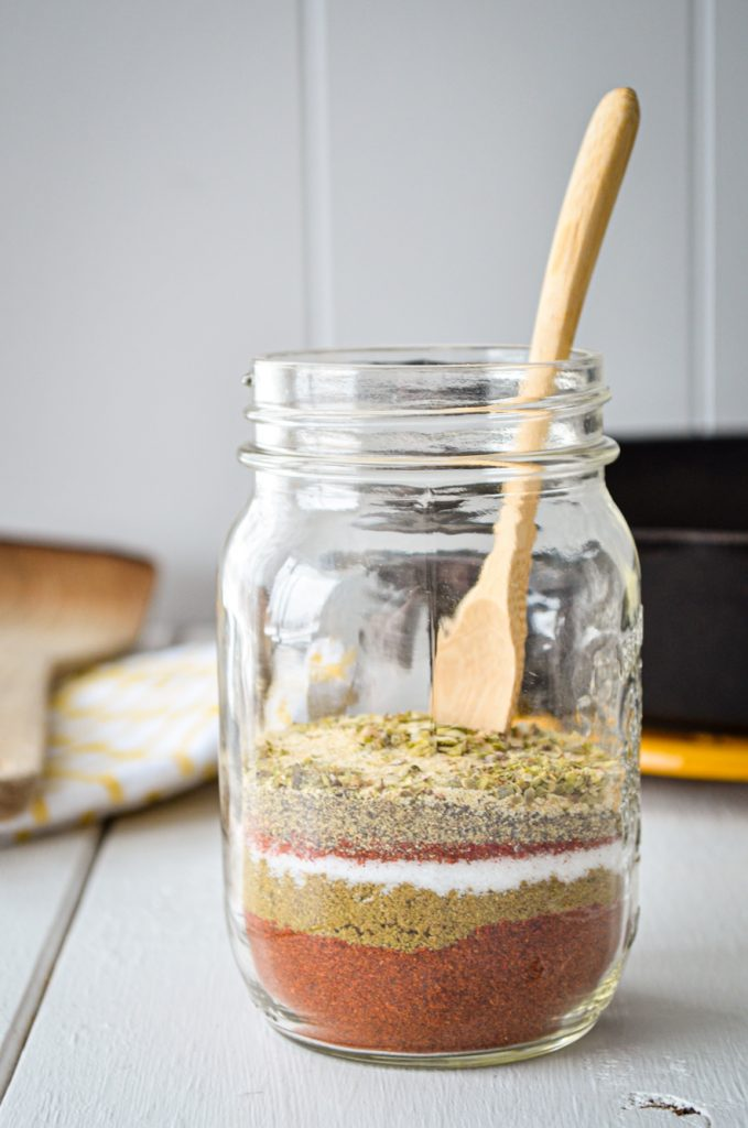 A jar of layered spices with a small wooden spoon inside. A cast iron skillet, wooden spatula, and tea towel are in the background.