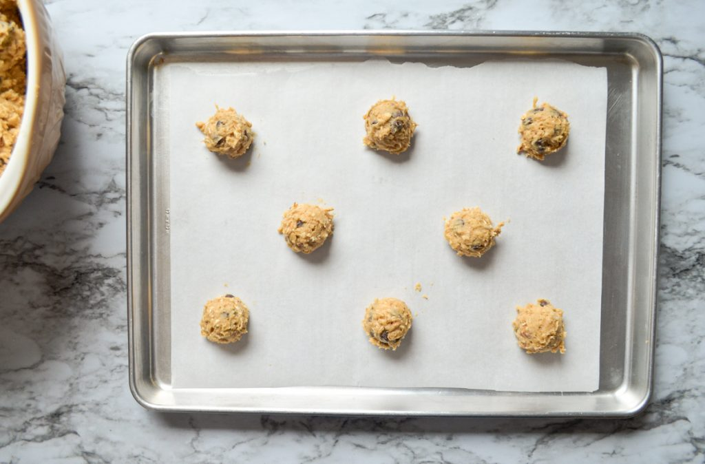 An overhead shot of cookies portioned onto a cookie sheet.