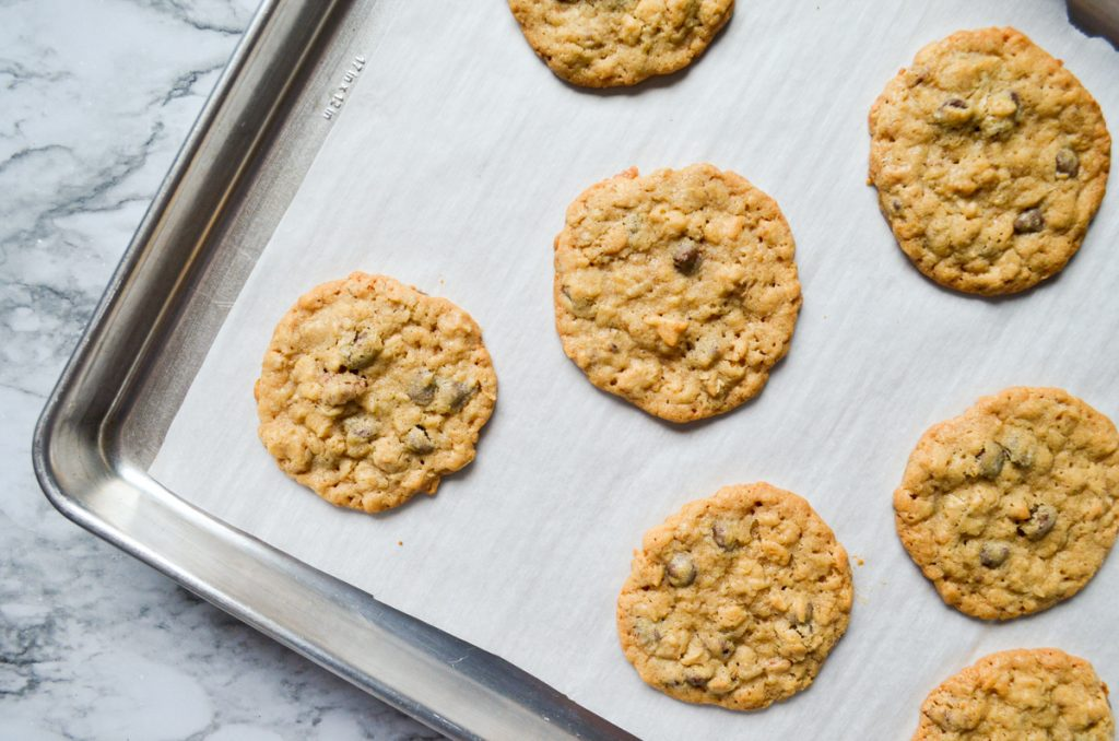 An overhead view of a baking sheet with baked cookies on parchment paper.