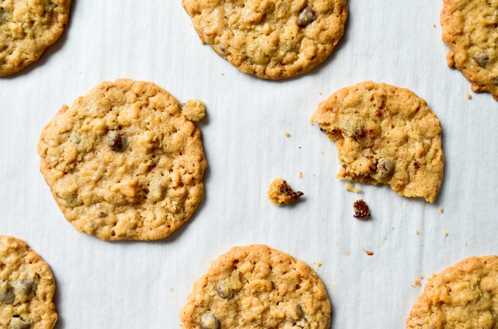 An overhead view of cookies, with a few crumbs of chocolate chip dough.