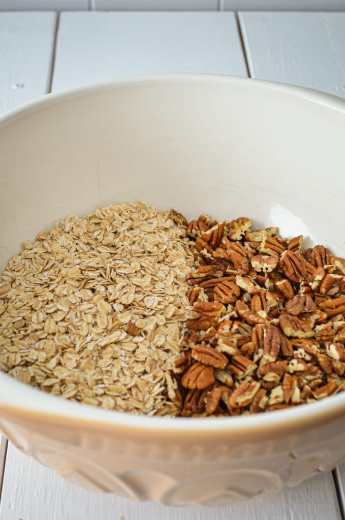 A large mixing bowl, containing dry oats and pecans.
