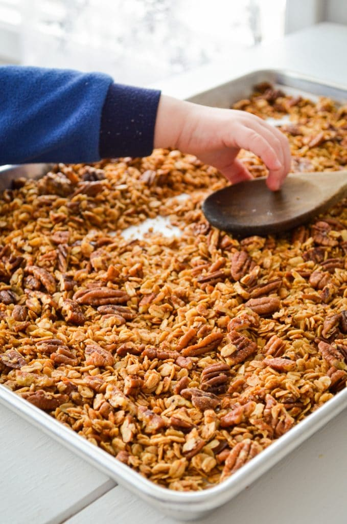 A toddler hand reaches in to grab a wooden spoon from a sheet pan of butter pecan granola.