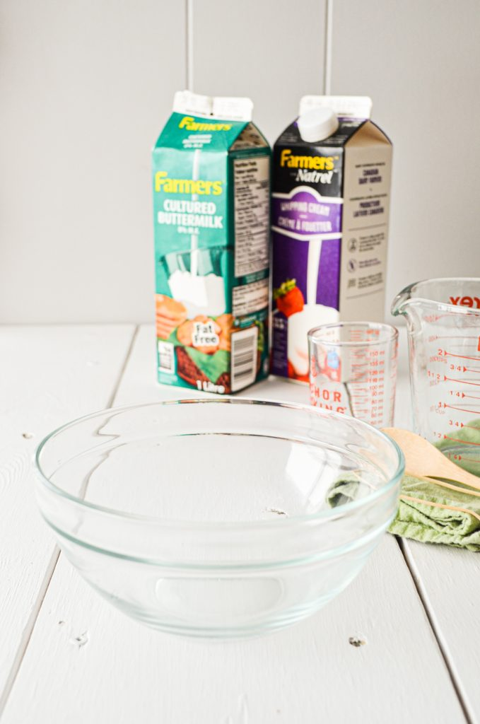 A glass bowl rests on a table, with a carton of heavy cream and a carton of buttermilk in the background.