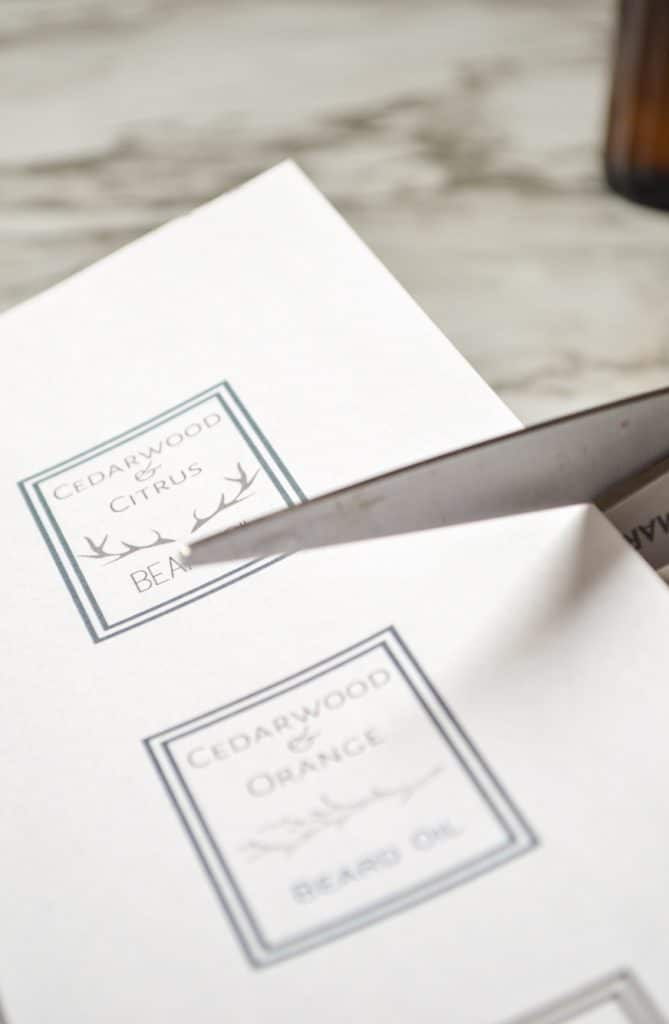 Scissors cutting into a sheet of labels.