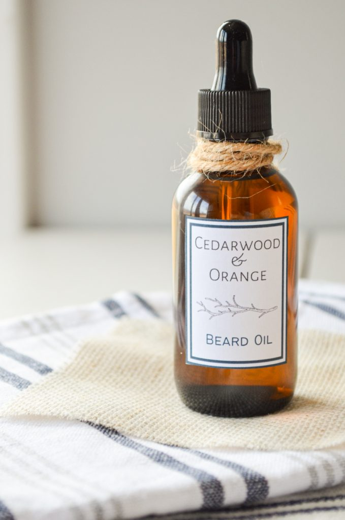 A bottle of Cedarwood and Orange beard oil. Placed on top of several cloth napkins and tied with a piece of twine.