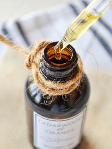 An oil dropper at the top of an amber bottle of beard oil. A bit of twine wrapped around the top.