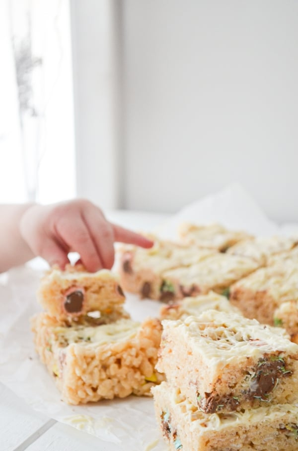 A toddler hand reaches in to grab a rice krispie treat.