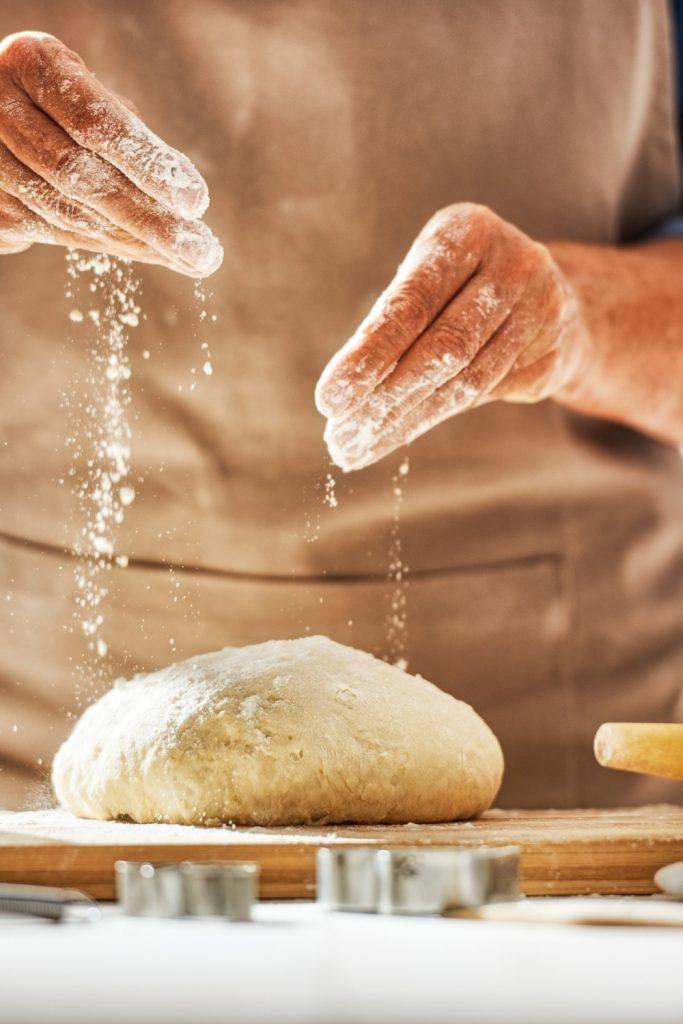 Hands sprinkling flour on bread dough.