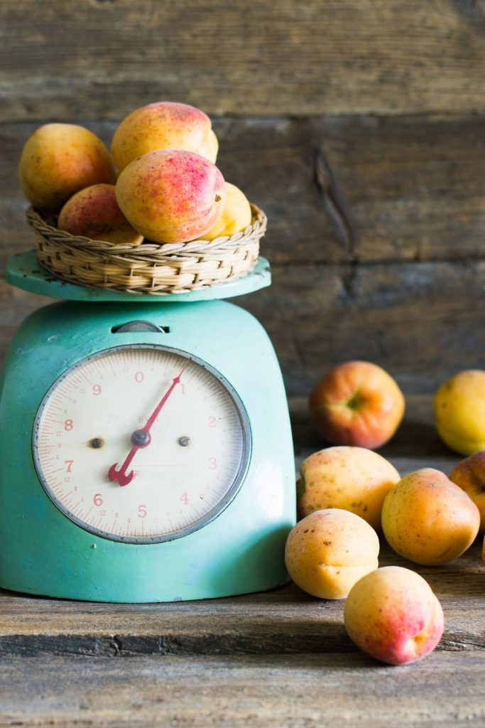 A large analog scale with peaches on it.