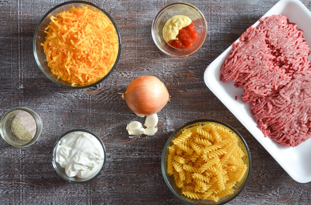 An overheat shot of ingredients including: ground beef, pasta, onion, garlic, cheddar cheese, sour cream, seasoning, ketchup, and mustard.