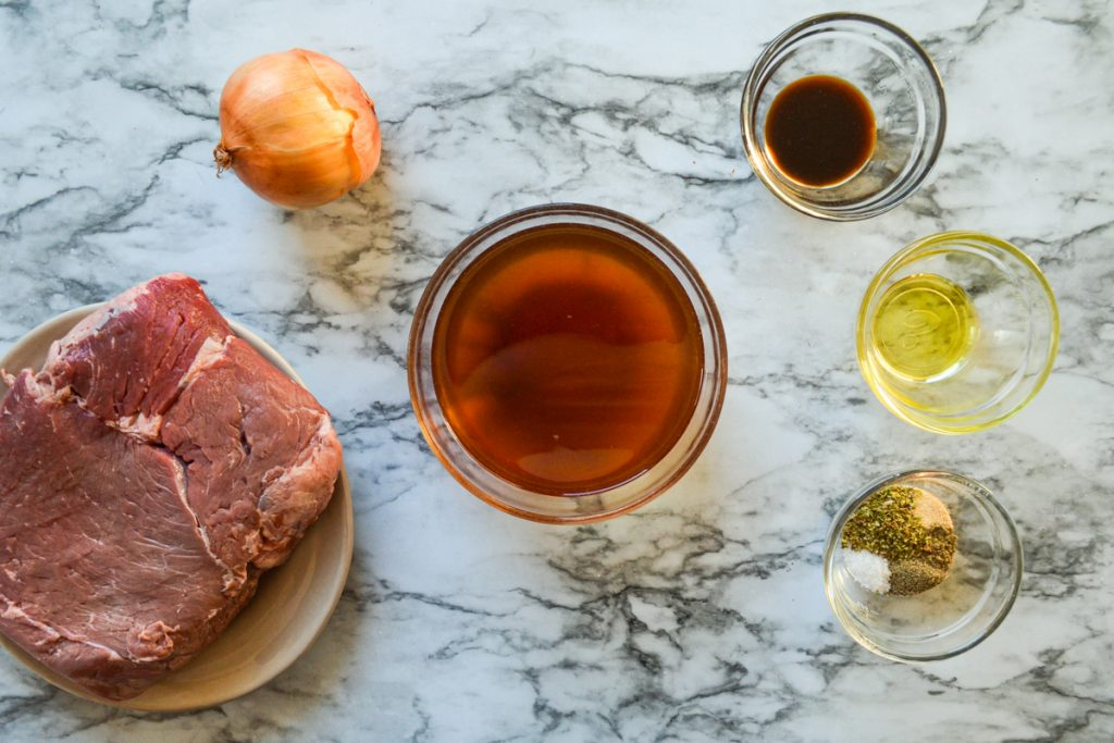 The ingredients needed to make Crockpot French Dip Sandwiches: beef, beef broth, seasonings, onion, worcestershire sauce, and oil.