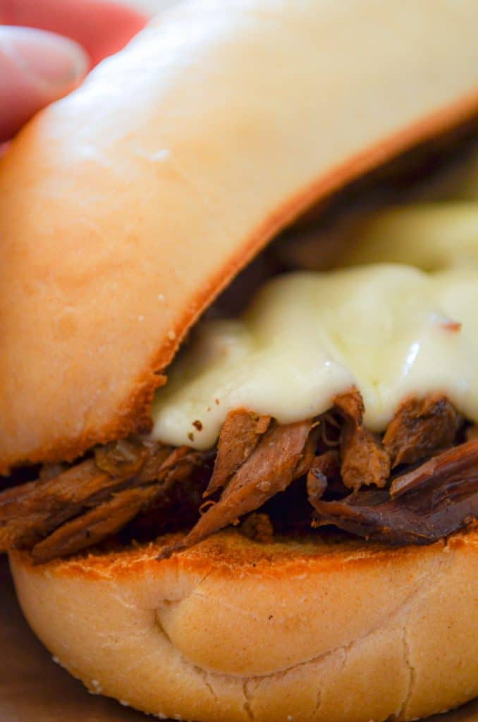 A close up of a french dip sandwich with melted provolone cheese.