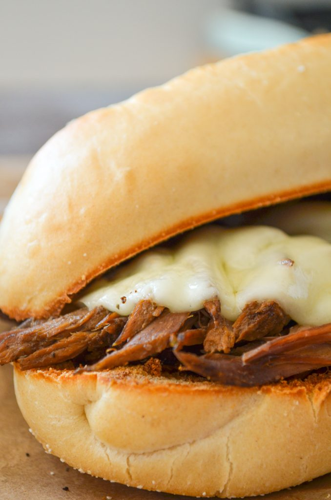 A french dip sandwich, featuring melted provolone cheese.