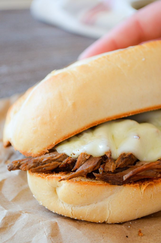 A french dip sandwich with melted provolone cheese.