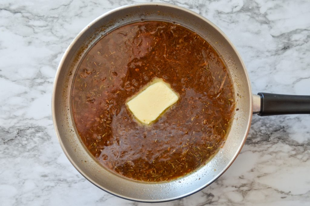 A pat of butter is placed on top of meat drippings in a skillet.