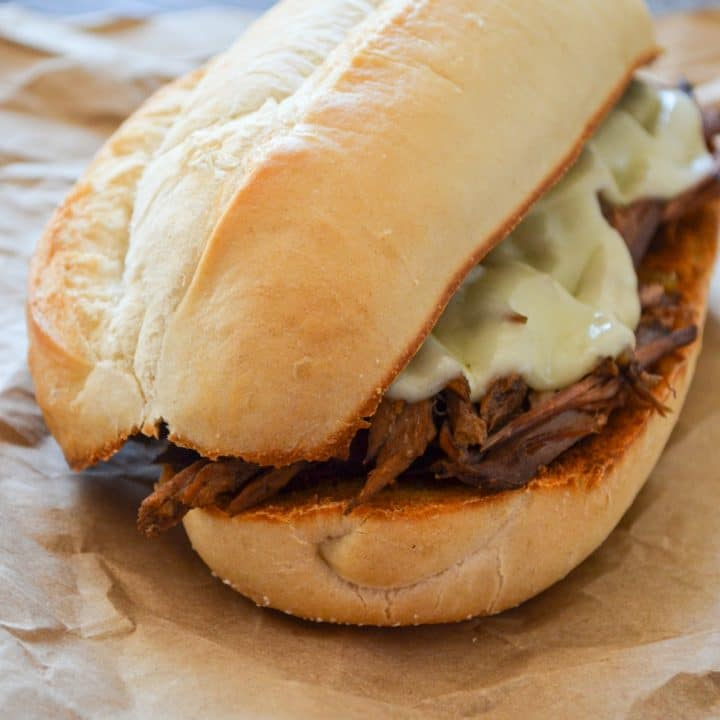 A french dip sandwich, resting on some brown paper.