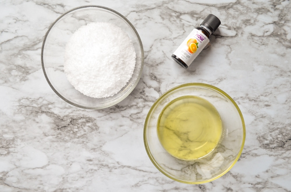 An overhead view of the ingredients needed for Facial salt scrub: Coconut oil, jojoba oil, orange essential oil, and coarse salt.
