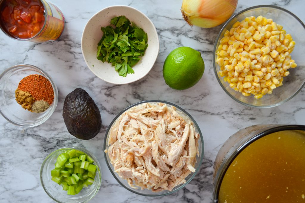 The ingredients needed for Mexican Chicken soup: chicken broth, cooked and shredded chicken, corn, cilantro, lime, onion, celery, rotel, and seasonings to name a few.