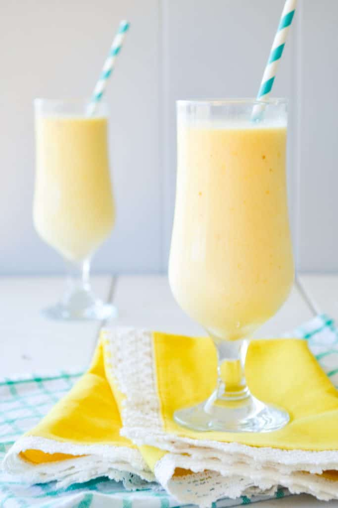 Two glasses of smoothies on a yellow napkin with paper straws sticking out.