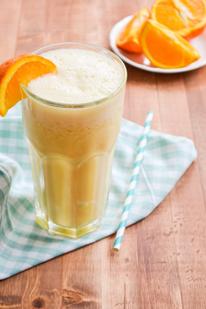 A glass of copycat orange julius, a plate of sliced oranges in the background.