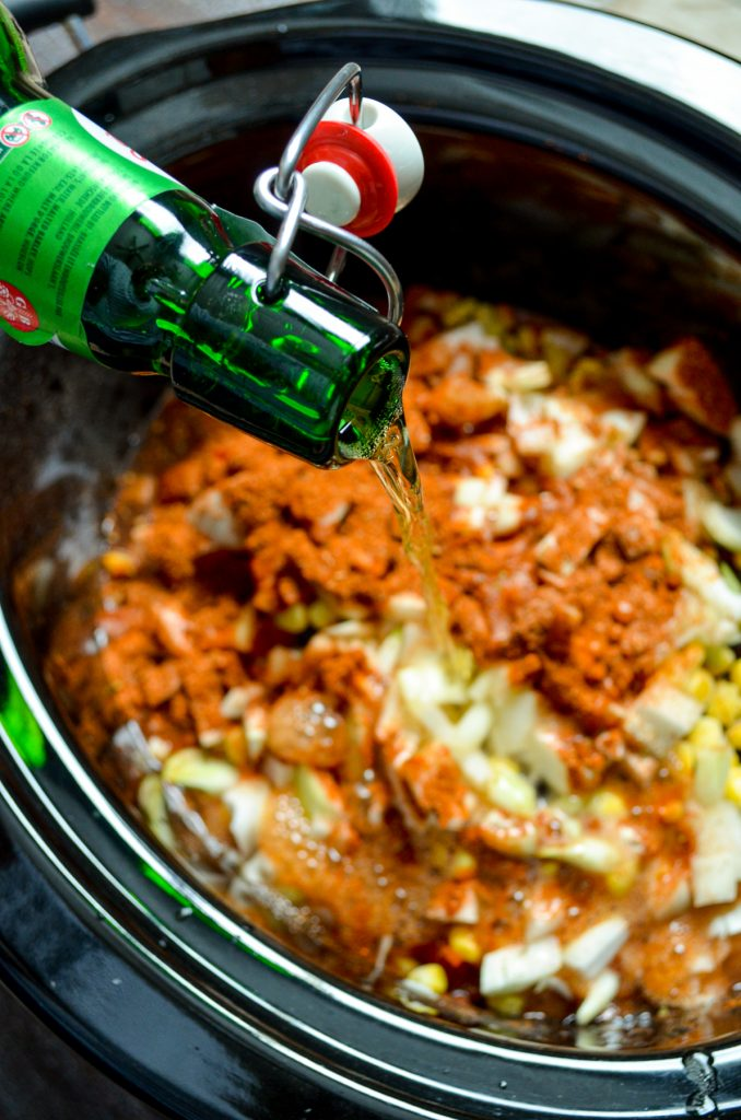 A bottle of beer being poured into a slow cooker full of chicken taco soup.