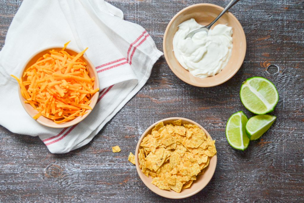 Topping suggestions for chicken taco soup include shredded cheese, crushed tortilla chips, sour cream, and lime wedges.