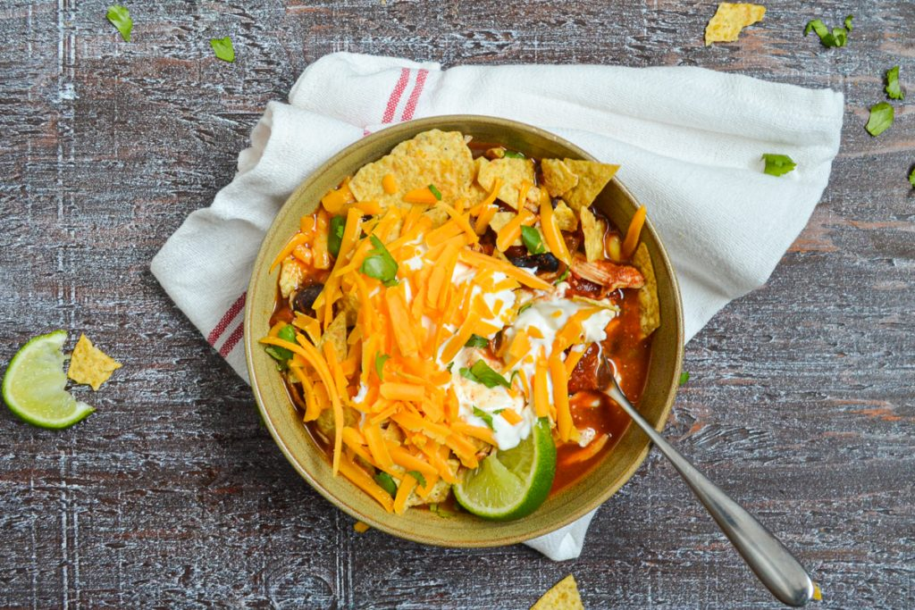 A bowl of chicken taco soup, topped with shredded cheese, sour cream, crushed tortilla chips, and lime wedges.