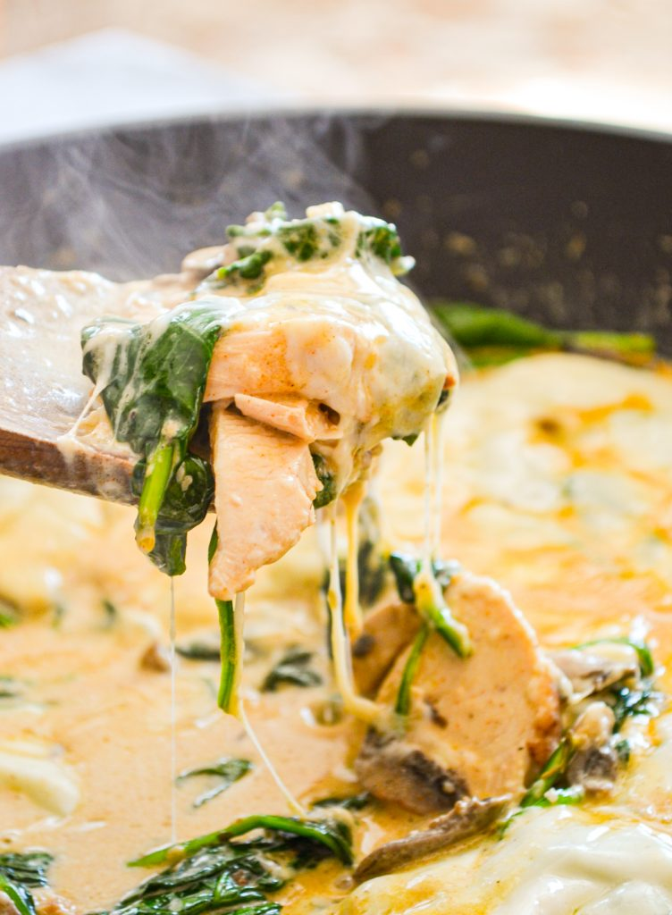 Spinach, mushroom and chicken skillet meal, with a wooden spoon pulling up a portion.