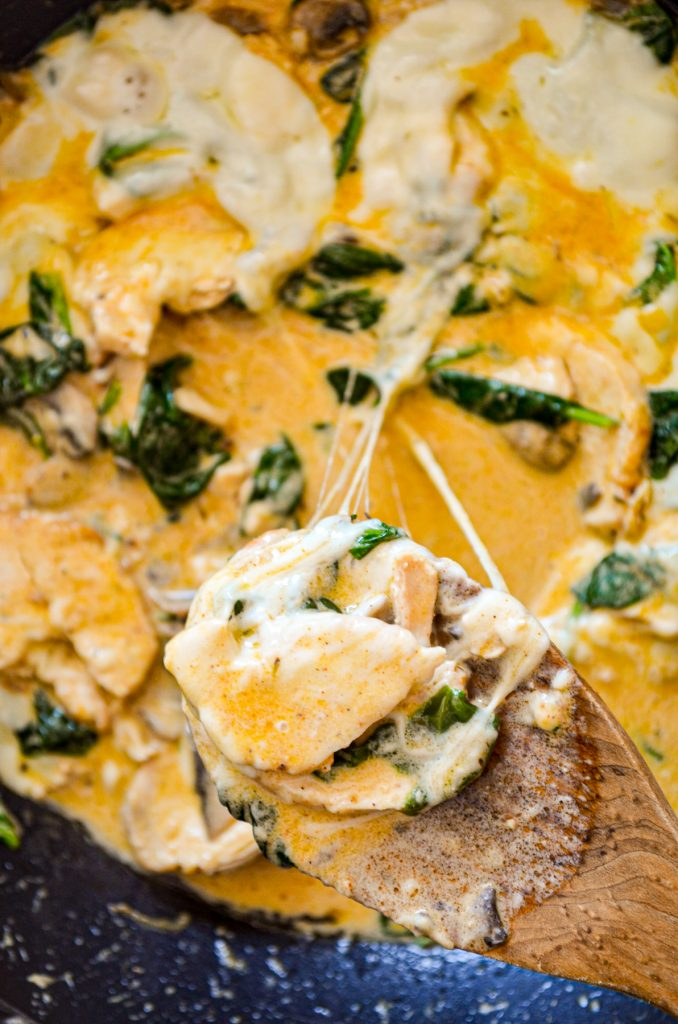 A wooden spoon pulling up a portion of a low carb skillet meal, the cheese stretching.