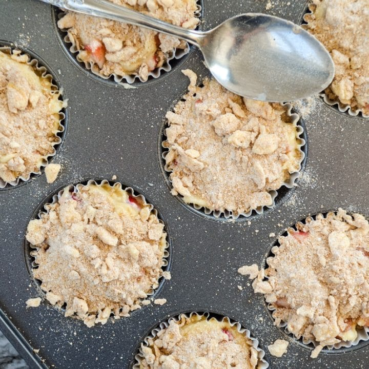 Muffins in a muffin tin, with a streusel topping. A spoon resting on the muffin tin.